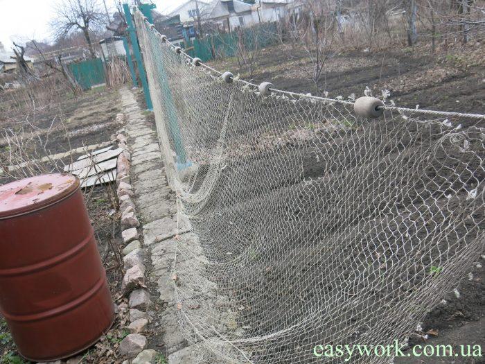 Бредень, растянутый во дворе на веревке