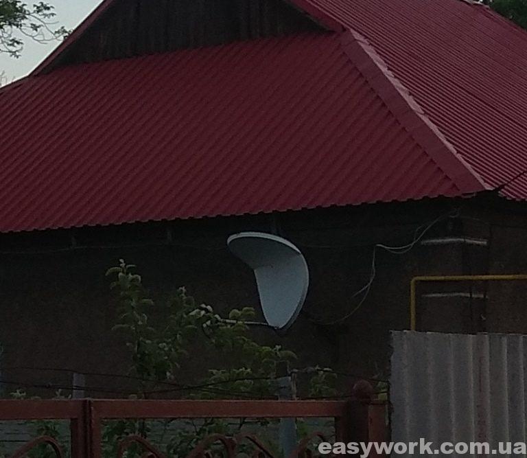Погнутая спутниковая тарелка от съехавшего снега с крыши