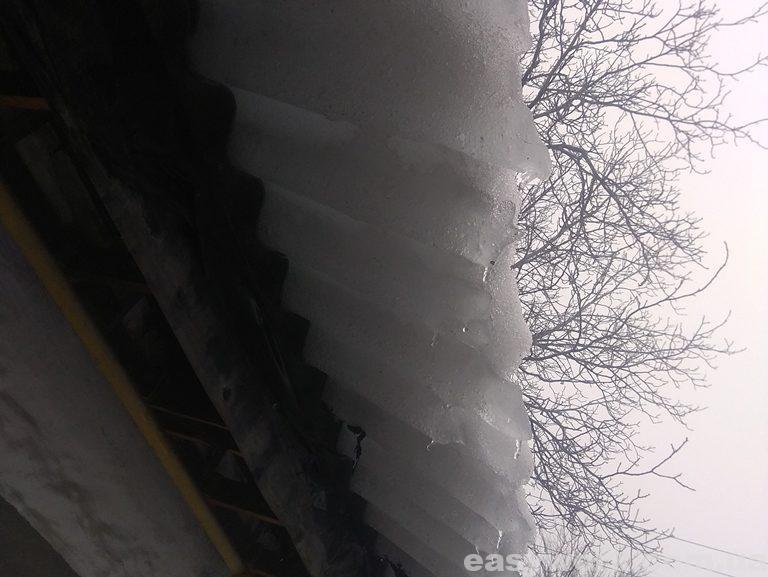 Ледяной снег над головой свисающий с крыши