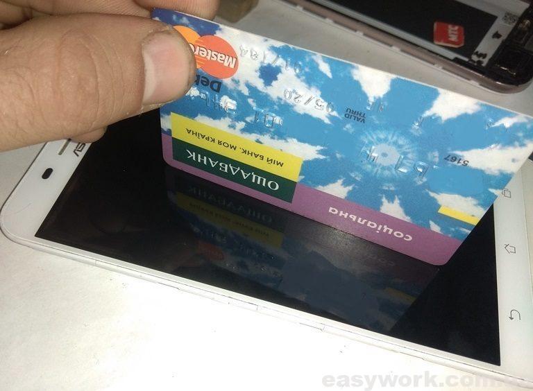 Отражение банковской карточки на экране телефона